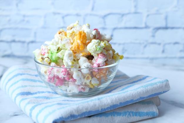 Kleurrijke popcorn in een kom op houten bureau
