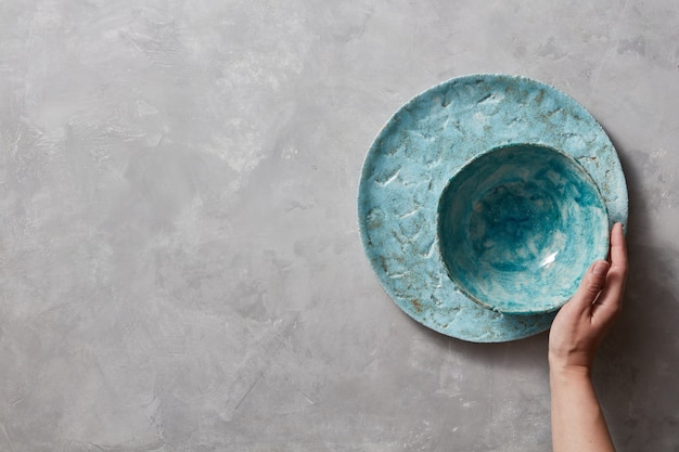 Kleurrijke porseleinen vintage handgemaakte schalen op een grijs marmeren tafel met ruimte voor tekst. vrouw neemt een blauwe keramische kom in haar hand. bovenaanzicht.
