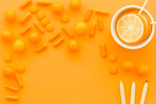 Kleurrijke potloden dichtbij lollys en suikergoed op oranje achtergrond