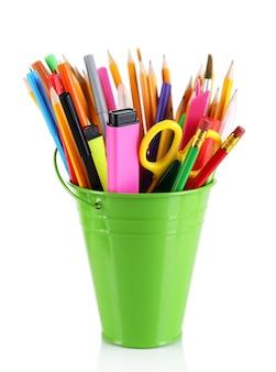 Kleurrijke potloden en andere kunstbenodigdheden in emmer geïsoleerd op wit