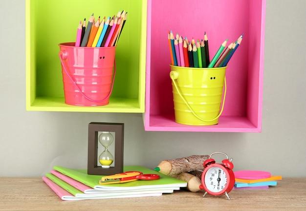 Kleurrijke potloden in emmers op planken op beige