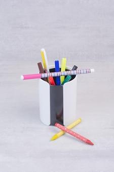 Kleurrijke potloden in etui op witte tafel.