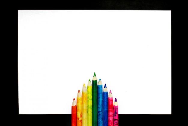 Kleurrijke potloden op een stuk papier liggen prachtig