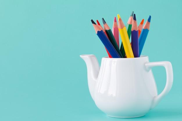 Kleurrijke potlood ingesteld op tafel op blauwe achtergrond