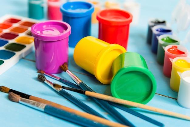 Kleurrijke potten met gouache en aquarellen op een blauwe achtergrond.