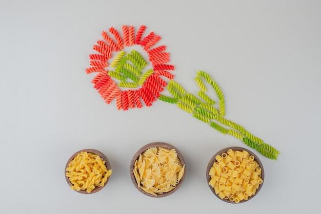 Kleurrijke rauwe macaroni als bloem op wit