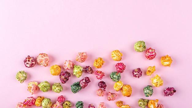 Kleurrijke regenboog karamel snoep popcorn op roze achtergrond. bioscoop snack concept. kijken naar film en entertainment achtergrond. ruimte voor tekst kopiëren, plat leggen.