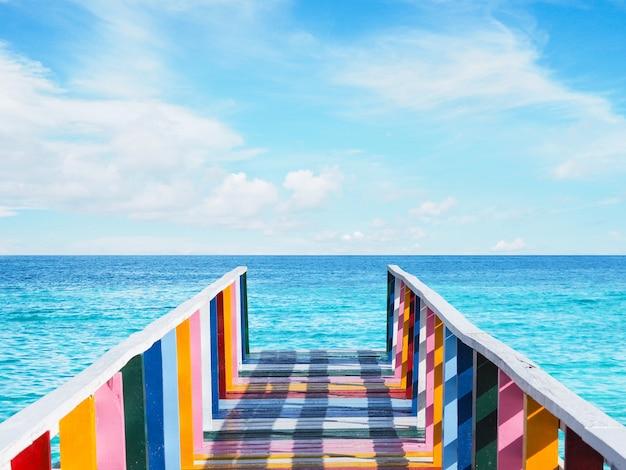 Kleurrijke regenboog vintage houten brug over de zee over blauwe hemelachtergrond bij pier.
