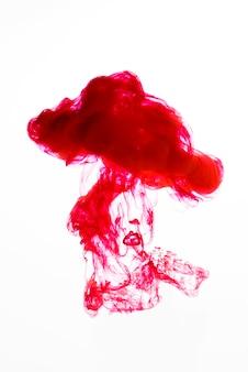 Kleurrijke rode daling die in water valt