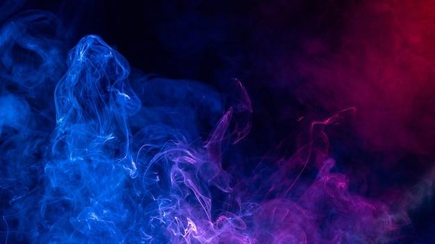 Kleurrijke rode en blauwe kleurenrook die op zwarte achtergrond wordt geïsoleerd