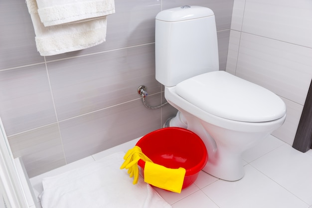 Kleurrijke rode wasbak, gele handschoenen en doek om schoon te maken in een badkamer die op de grond staat naast een effen wit toilet