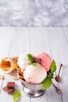 Kleurrijke roomijslepels en aroma's met bessen, chocolade en munt op houten achtergrond