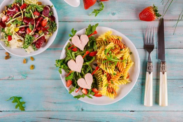 Kleurrijke rotini-pasta, kerstomaatjes, harten van hotdogs en salade. valentijnsdag concept.