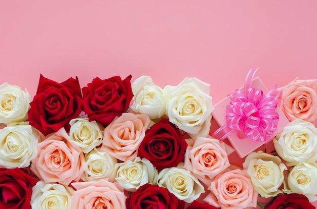 Kleurrijke rozen zetten op roze oppervlak met roze geschenkdoos voor san valentijnsdag