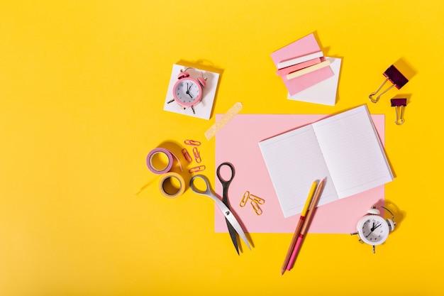 Kleurrijke samenstelling van vrouwelijke kantoorbehoeften in roze kleuren die op oranje muur liggen