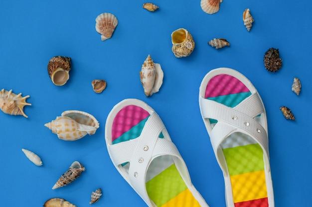 Kleurrijke schoenen en veel zeeschelpen op een blauwe achtergrond. het concept van een vakantie aan zee. plat leggen. het uitzicht vanaf de top.