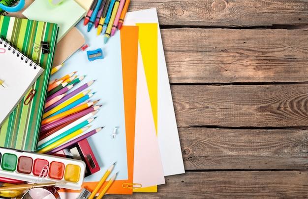 Kleurrijke schoolbenodigdheden op houten tafel achtergrond