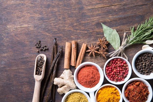 Kleurrijke selectie van kruiden en specerijen. aromatische ingrediënten op houten tafel