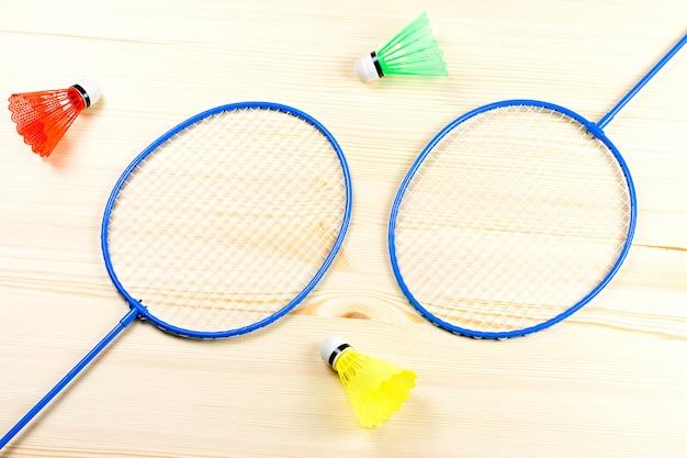 Kleurrijke shuttles en badmintonrackets plat op houten blad