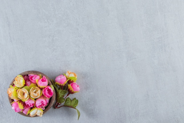 Kleurrijke sierlijke bloemen in een kom, op de witte tafel.