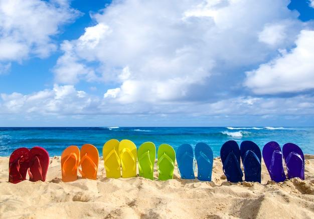 Kleurrijke slippers op het zandstrand