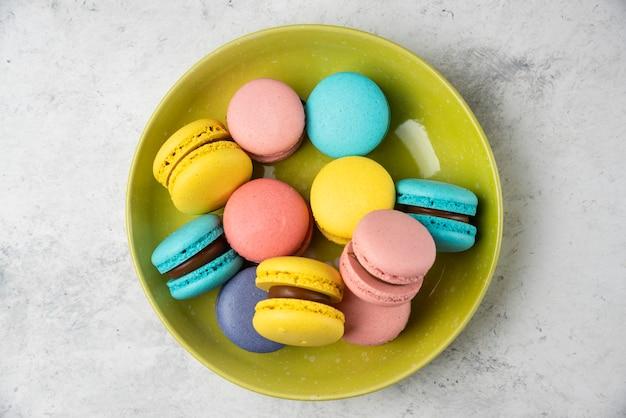Kleurrijke smakelijke macarons op groene plaat en op witte tafel.