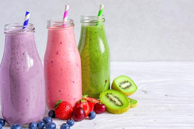 Kleurrijke smoothiedranken in flessen met vers fruit en bessen