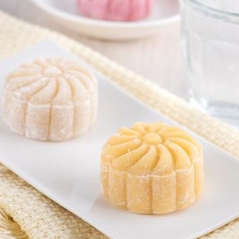 Kleurrijke sneeuw huid maancake, zoete besneeuwde mooncake, traditioneel hartig dessert voor mid-autumn festival op lichte houten achtergrond, close-up, levensstijl.
