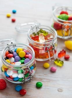 Kleurrijke snoepjes, gelei en marmelade in potten op tafel