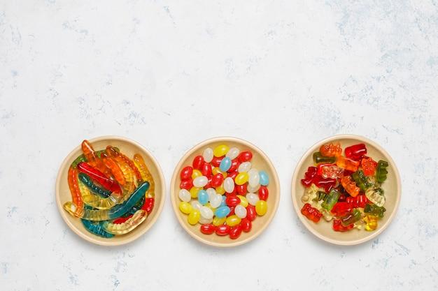 Kleurrijke snoepjes, gelei, marshmallow op lichte ondergrond. bovenaanzicht met kopie ruimte