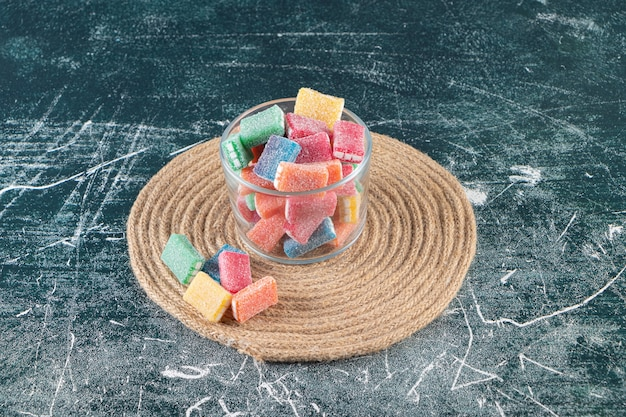 Kleurrijke snoepjes in een glazen kom op een onderzetter, op de gemengde tafel.