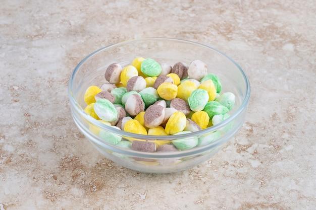 Kleurrijke snoepjes in een kom, op de marmeren tafel.