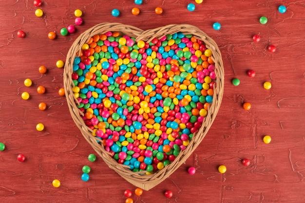 Kleurrijke snoepjes in het hart met rode achtergrond