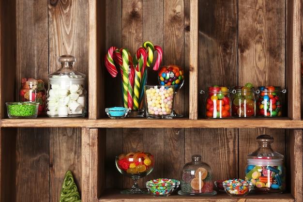 Kleurrijke snoepjes in potten op houten planken close-up