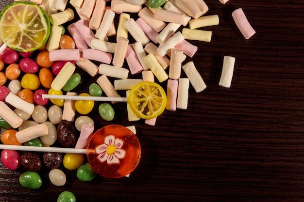 Kleurrijke snoepjes, lolly's en marshmallows op houten tafel