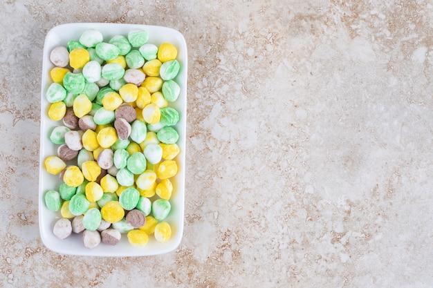Kleurrijke snoepjes op een bord, op het marmer.