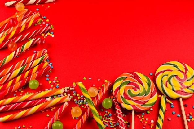 Kleurrijke snoepjes op een rood oppervlak