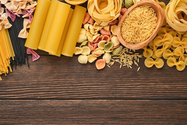 Kleurrijke spaghetti, tagliatelle, farfalle, penne, ptititm, noedels, fusilli, cannelloni op een oude houten achtergrond