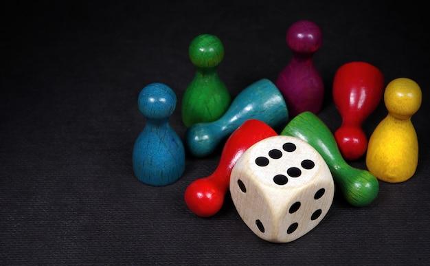 Kleurrijke speelfiguren met dobbelstenen op een zwart bord