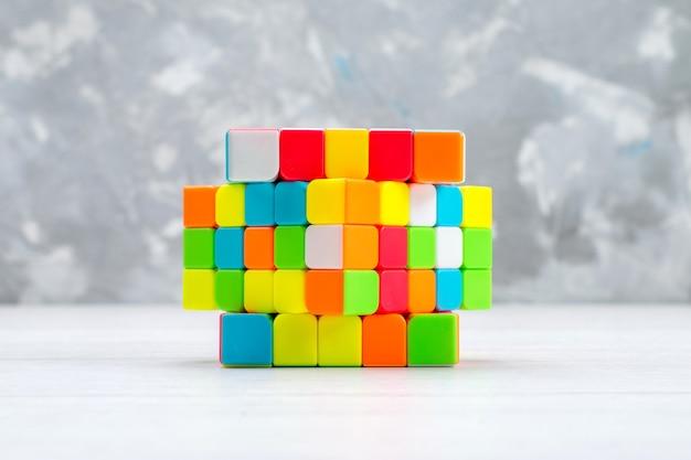 Kleurrijke speelgoedconstructies ontworpen en gevormd op een lichte, plastic rubberen kubus