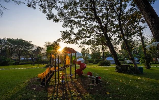 Kleurrijke speelplaats en zonsopgang op werf in het park