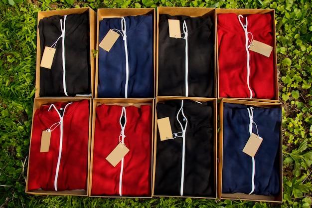 Kleurrijke sportkleding met tags gevouwen in kartonnen dozen liggen op de grond met gras.