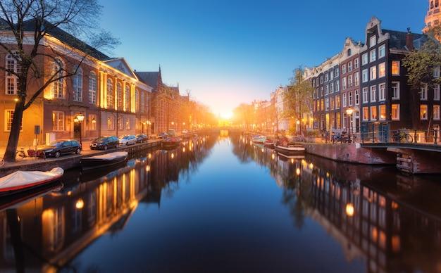 Kleurrijke stadsgezicht bij zonsondergang in amsterdam, nederland