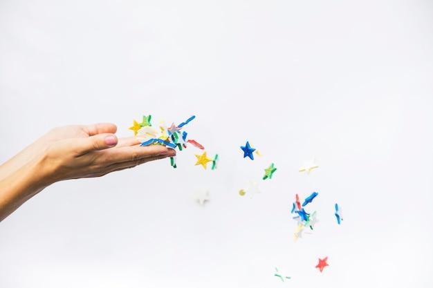 Kleurrijke sterren die van de vrouwelijke die handen blazen tegen witte achtergrond worden geïsoleerd