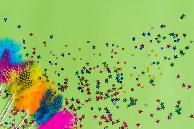 Kleurrijke stokken met confetti eronder op een groene tafel