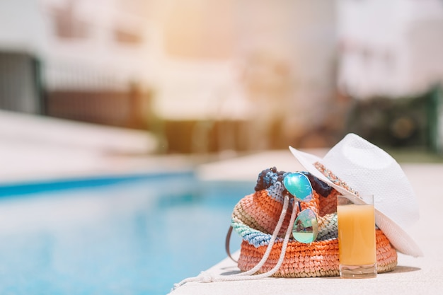 Kleurrijke strandtas, glas sap, strohoed en vliegtuigmodel