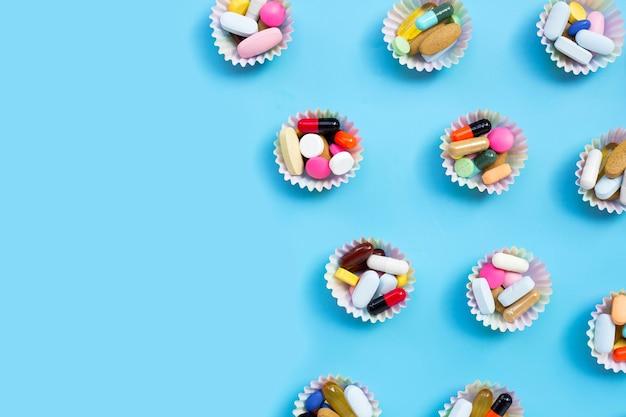 Kleurrijke tabletten met capsules en pillen in cupcake wrappers op blauw.