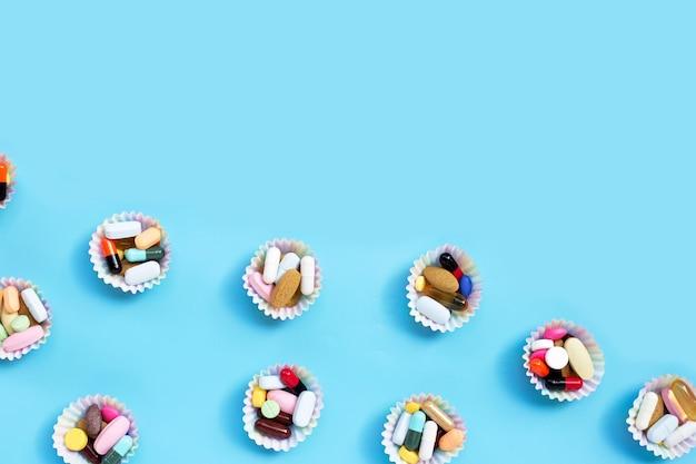 Kleurrijke tabletten met capsules en pillen in cupcake wrappers op blauwe achtergrond.