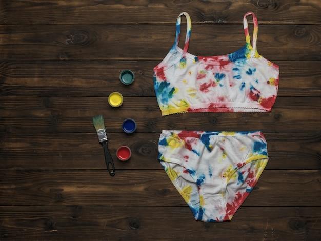 Kleurrijke textielverf en ondergoed in tie-dye-stijl op een houten tafel. gekleurd ondergoed in huis.