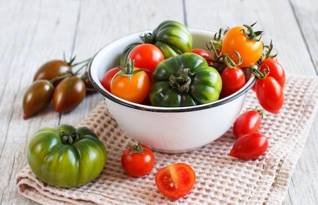 Kleurrijke tomaten in een kom op een houten tafel
